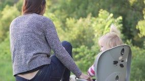 La mujer sujeta a una muchacha en una silla de la bicicleta metrajes
