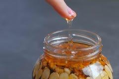 La mujer sumerge su finger en miel con las nueces en el tarro Mano, finger y tarro del primer en la tabla negra fotos de archivo libres de regalías