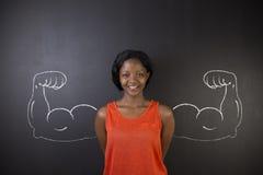 La mujer surafricana o afroamericana con el brazo fuerte sano muscles para el éxito foto de archivo
