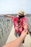 La mujer tailandesa lleva alguien por la mano y el control del puente de la calzada Imágenes de archivo libres de regalías