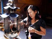 La mujer tailandesa ruega con la flor, el palillo de ídolo chino y la vela para el st de Buda Imagenes de archivo