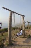 La mujer tailandesa se sienta y el juego en banco de madera balancea el juguete Imágenes de archivo libres de regalías