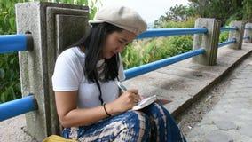 La mujer tailandesa sienta y escribe la nota en el libro para la memoria del detalle entre el viaje almacen de metraje de vídeo