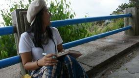 La mujer tailandesa sienta y escribe la nota en el libro para la memoria del detalle entre el viaje metrajes