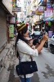 La mujer tailandesa toma la foto en la calle en el mercado de Thamel Fotografía de archivo