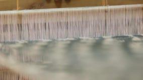 La mujer teje una tela en un telar Cámara lenta