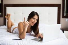 La mujer tiene idea y escribe esto en ordenador portátil en ordenador de la cama Imágenes de archivo libres de regalías