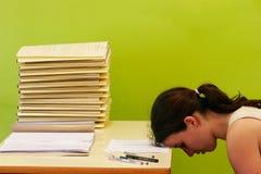 La mujer tiene tensión debido a trabajo enorme sobre su escritorio Imagenes de archivo
