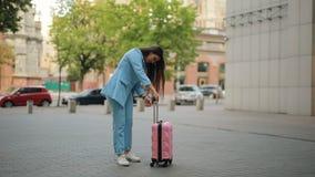 La mujer tiene un problema típico con su maleta en ciudad, maneja no la diapositiva hacia fuera almacen de metraje de vídeo
