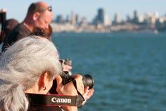 La mujer tira las fotos de San Francisco Skyline On Ferry Trip Imagen de archivo libre de regalías