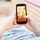 La mujer todavía toca smartphone con vida de Navidad del oro Foto de archivo