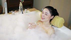 La mujer toma el baño de burbujas y jugar en bañera almacen de metraje de vídeo