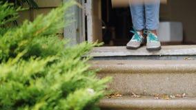 La mujer toma el paquete del umbral de su casa En el marco, solamente la puerta, la caja y las piernas del almacen de video