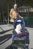 La mujer toma el perro blanco en el cochecillo de bebé para un Central Park del paseo abajo en Manhattan, New York City, Nueva Yo Imágenes de archivo libres de regalías
