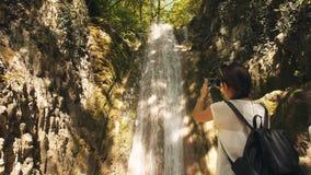 La mujer toma la foto de la cascada almacen de video