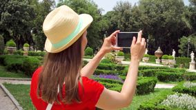 La mujer toma la foto del parque en el teléfono móvil en la cámara lenta Turísticos femeninos toman la imagen en el chalet Borghe metrajes