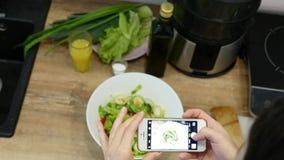 La mujer toma la foto en el teléfono elegante y pone en hojas del marco de la ensalada verde y del pepino con el tomate rojo metrajes