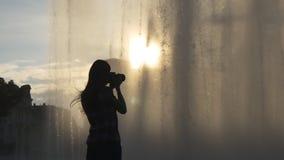 La mujer toma imágenes de los descensos de la fuente metrajes