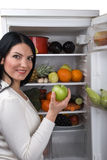 La mujer toma la manzana verde del refrigerador Fotos de archivo