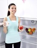 La mujer toma la manzana y la leche rojas del refrigerador imagen de archivo