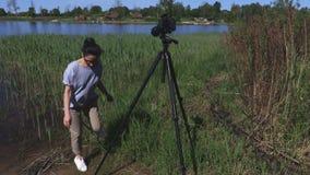 La mujer toma las fotos cerca del lago almacen de metraje de vídeo
