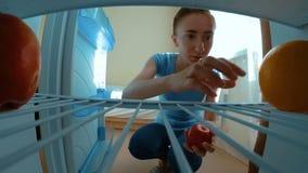 La mujer toma las frutas del refrigerador almacen de metraje de vídeo