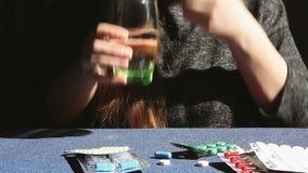 La mujer toma la medicina - cápsula y vaso de agua azules, concepto de la atención sanitaria almacen de metraje de vídeo