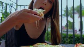 La mujer toma la rebanada apetitosa de pizza caliente con estirar el queso almacen de video