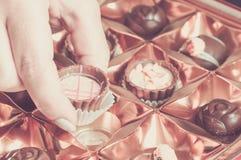 La mujer toma un chocolate de la caja Fotografía de archivo libre de regalías
