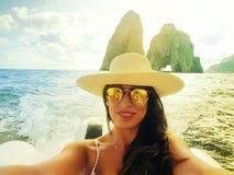 La mujer toma un selfiet cerca del Faraglioni de la isla de Capri imagenes de archivo