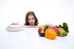 La mujer toma una decisión entre la torta Fotografía de archivo