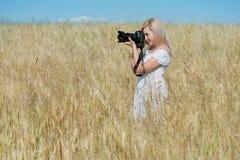 La mujer toma una foto con la cámara en un campo foto de archivo