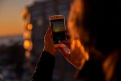 La mujer toma una foto de la puesta del sol con la sombra de la ciudad Imagenes de archivo