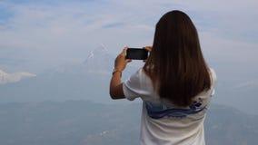 La mujer toma una imagen de las montañas en un móvil metrajes