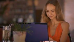 La mujer trabaja con el cóctel de consumición del ordenador portátil en café