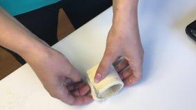 La mujer trabaja con la pasta de hojaldre Los envuelve un cubilete de cristal almacen de metraje de vídeo