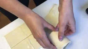 La mujer trabaja con la pasta de hojaldre Los envuelve un cubilete de cristal metrajes