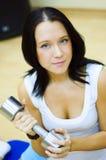 La mujer trabaja con pesa de gimnasia. Imagenes de archivo