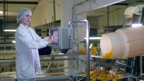 La mujer trabaja con una máquina de la fábrica, controlando un transportador con los microprocesadores almacen de metraje de vídeo