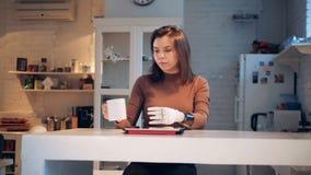 La mujer trabaja con una tableta, prótesis robótica que lleva, cierre para arriba almacen de metraje de vídeo