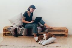 La mujer trabaja de hogar en el ordenador portátil con el perro Foto de archivo libre de regalías