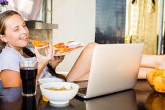 La mujer trabaja en el ordenador y la consumición de los alimentos de preparación rápida Vida malsana Fotos de archivo