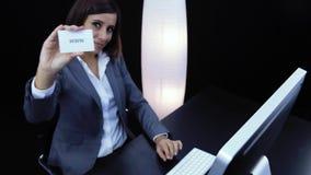 La mujer trabaja en el ordenador y mostrar una tarjeta con el texto almacen de video
