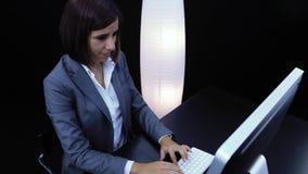 La mujer trabaja en el ordenador y mostrar una tarjeta con el texto almacen de metraje de vídeo