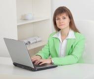 La mujer trabaja en la oficina con el ordenador Fotografía de archivo