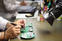 La mujer trabaja en montaje manual del circuito impreso electrónico b Imágenes de archivo libres de regalías