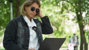 La mujer trabaja en un ordenador portátil mientras que se sienta en parque metrajes