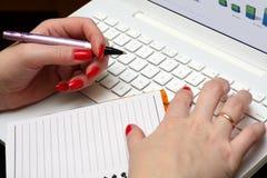 La mujer trabaja en una computadora portátil blanca. foto de archivo libre de regalías