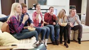 La mujer trae las palomitas a sus amigos y ven la TV almacen de metraje de vídeo