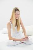 La mujer tranquila contenta que manda un SMS con su smartphone que se sienta en ella sea Fotos de archivo libres de regalías
